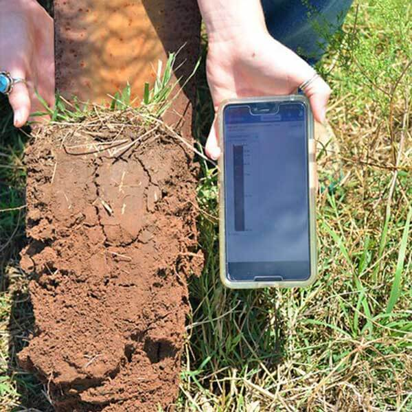 Person holding soil in one hand and a cell phone with the Soil app in the other hand