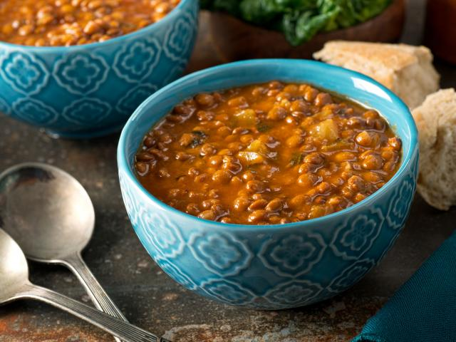 A blue bowl filled with lentil soup on a table