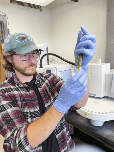 ARS microbiologist, Kevin Panke-Buisse inspects the two-chambered vial filed with milk, indicator dye, and a urease enzyme