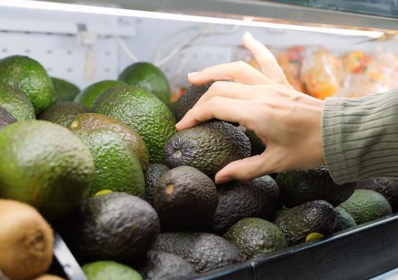 Closeup of a shopper's hand picking an avocado in a grocery store bin