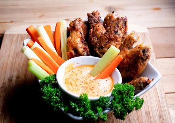 Bowl of chicken wings, cup of hot sauce, carrot and celery sticks with parsley