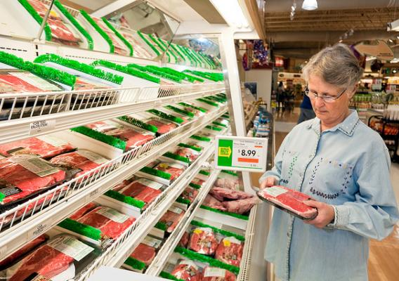 A shopper examines a package of meat in a grocery store for freshness