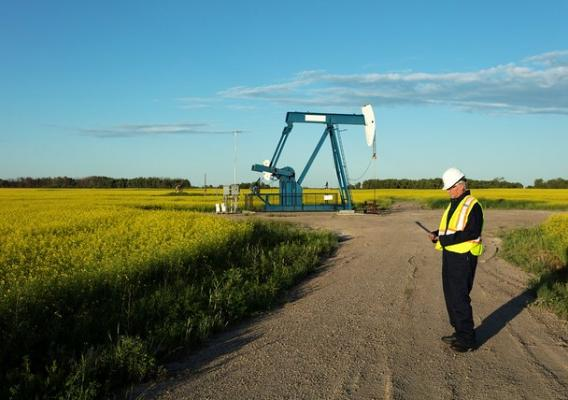A man in front of an oil pump