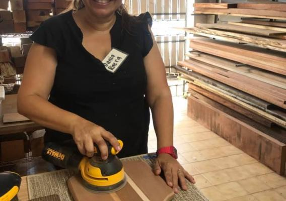 Woman making a cutting board with wood salvaged from Hurricane Maria