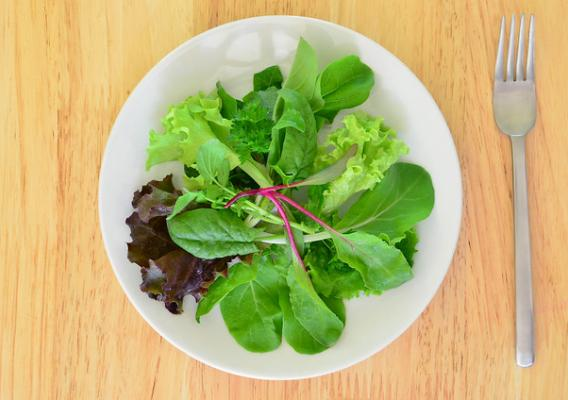 Fresh baby greens in a salad on wood table