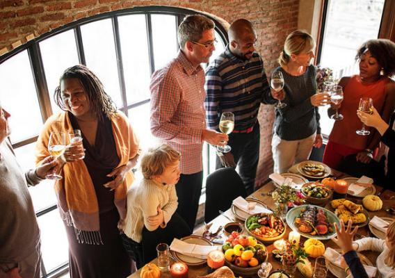 People gathering around Thanksgiving table