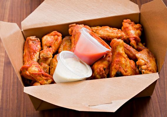 A box of chicken wings and sauces