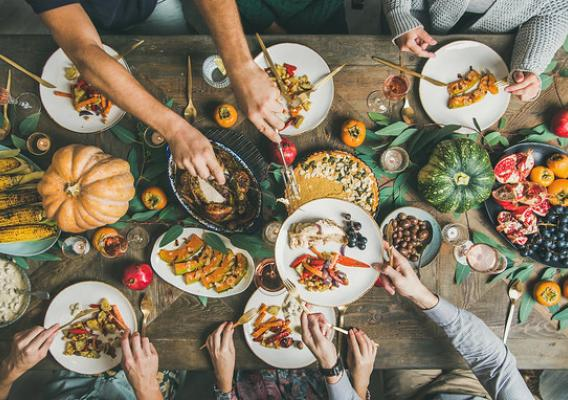 Flat-lay of friends or family feasting at Thanksgiving Day festive table with turkey, pumpkin pie, roasted seasonal vegetables and fruit, top view