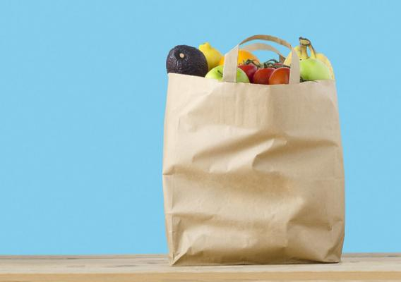 A paper grocery bag filled with healthy groceries