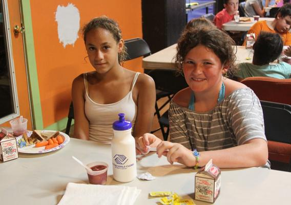 Students with their school meals at a table