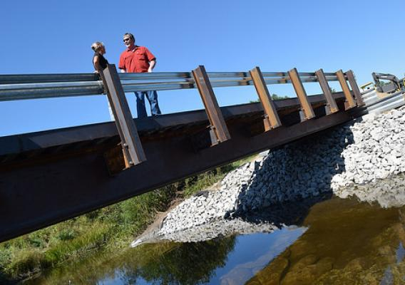 NRCS District Conservationist Wayne Munroe (right) talking with farm owner Cynthia Hodak on the bridge