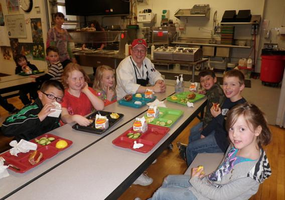 Students sitting and eating their lunch with School Chef Jason Moore
