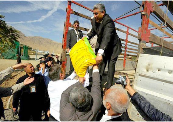U.S. Ambassador to Afghanistan Karl Eikenberry (front in white) and Afghan Agriculture Minister Asif Rahimi (on truck) load seed At Badam Bagh Farm in Kabul.