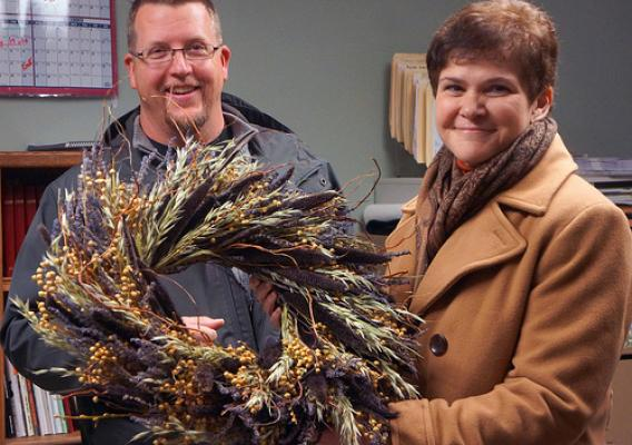 Ralph Cramer shows Deputy Harden some of the wreaths created with dried flowers from Cramer's Posie Patch.