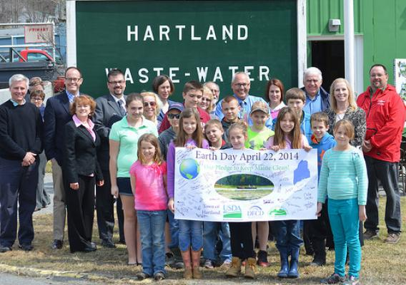 USDA Rural Development State Director Virginia Manuel (back row second from right) announced Earth Day funds in the amount of $29.7 million to assist rural wastewater systems in Maine, including the Town of Hartland. Children from the Hartland community took time away from their school vacation to sign the official USDA Earth Day Banner.