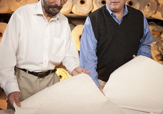 ARS cotton technologist Paul Sawhney (left) and research leader Brian Condon examine needled-punched nonwoven products made with classical raw cotton and precleaned raw cotton, respectively.