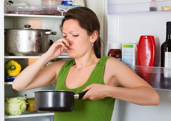 A woman holding her nose at spoiled food in the pot in front of the refrigerator