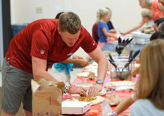 "Arizona Cardinals football player Drew Butler making pizza with kids at the Ken ""Chief"" Hill Learning Academy of the Chandler Unified School District in Arizona"