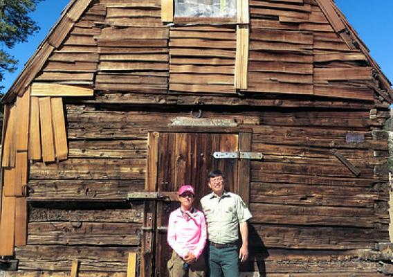 Current range permittee Lynn Sanguinetti and Fred Wong, U.S. Forest Service district ranger, stand in front of a cabin