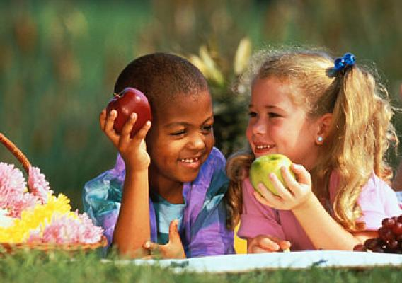A boy and girl smiling and holding fruits in their hands