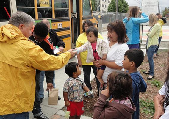 Volunteers distribute sack lunches to children at the New Freedom Park Summer Food Service Program site in Aurora, Colorado.  The lunches are delivered in a school bus by an organization called Lunch Box Express.