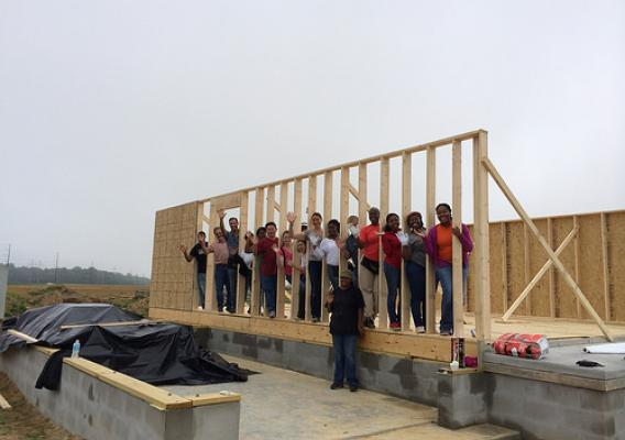USDA Rural Development employees join Mutual Self-Help Program participant Michelle Mosely for a break from installing floor beams to Michelle's future home.