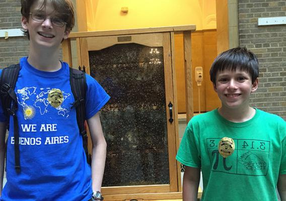 Josh Landweber and Jonah Docter-Loeb standing in front of their favorite exhibit for the day, the Agriculture Research Service's Bee Research Lab demo