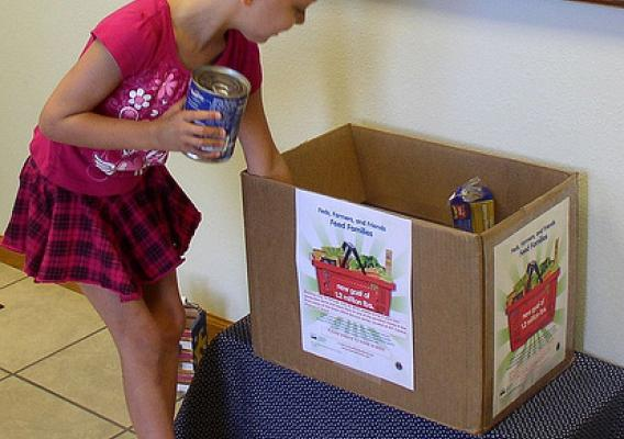 "Mackayla Wallin, age five, makes her contribution to feed the hungry in Grant, Neb. at the recent ""Feds, Farmers, and Friends Feed Families"" food drive."