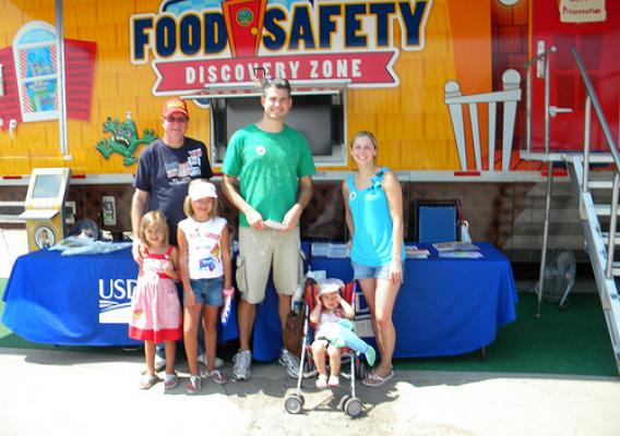 A BAC free family smiles in front of the Discovery Zone after learning to Clean, Separate, Cook, and Chill.