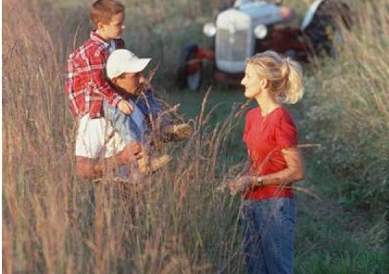 A family stands in a plot of tall grass plantings on a farm in central Iowa. NRCS photo.
