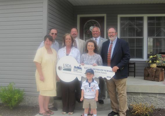 Rural Development employees with West Virginia homeowners in front of their new home.  Row 1:  Connor Sexton.  Row 2 (l to r):  Penny Thaxton (Housing Specialist); Shelly Hickman (Area Specialist); Homeowner Jamalyn Sexton; and Craig Burns (Area Director).  Row 3 (l to r):  Jeff Hunt (Area Specialist); David Cain (Acting Housing Program Director); and Bobby Lewis (State Director).