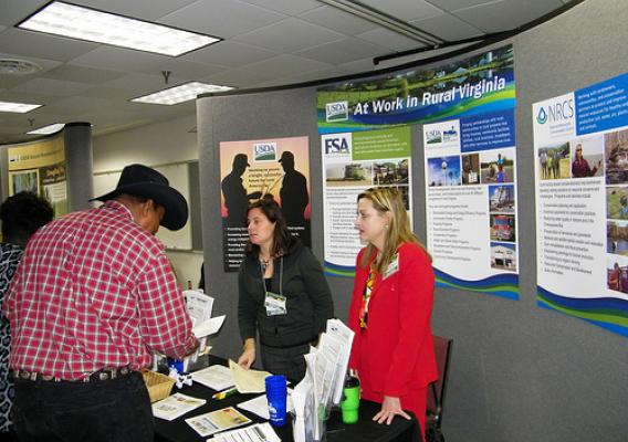 Linda Cronin (Left), Public Affairs Specialist for FSA and Janice Stroud-Bickes (Right) Area Director for Rural Development are reviewing USDA program details with local producer at the USDA information booth