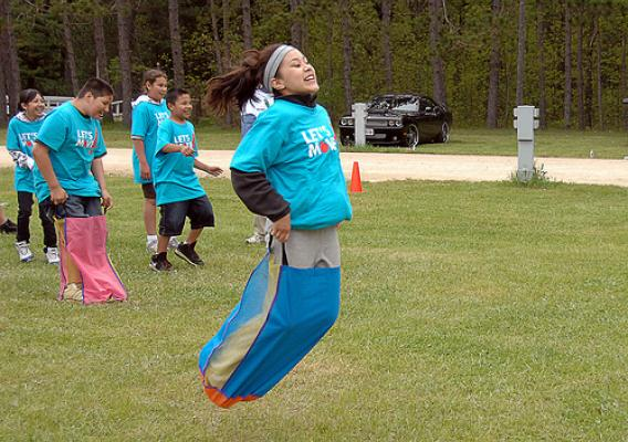 A Menominee girl enjoys the sackrace fun with her classmate friends.