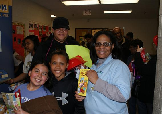 (from L to R) Kimberly Mejia and Germany Ray, both Oxon Hills Elementary School students, Felicia Thompson and Nita Ray stop by the FSIS food safety exhibit to obtain food safety information, educational materials and promotional items during the Oxon Hills Health Extravaganza on March 23, 2011.