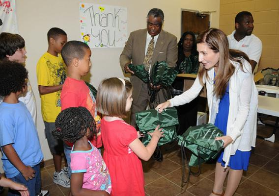 FNS Deputy Administrator Lisa Pino (right) and Southeast Regional Administrator Don Arnette (left) hand out meals and backpacks to kids at a Salvation Army summer feeding site in Marietta, GA during National Summer Food Service Program Week.