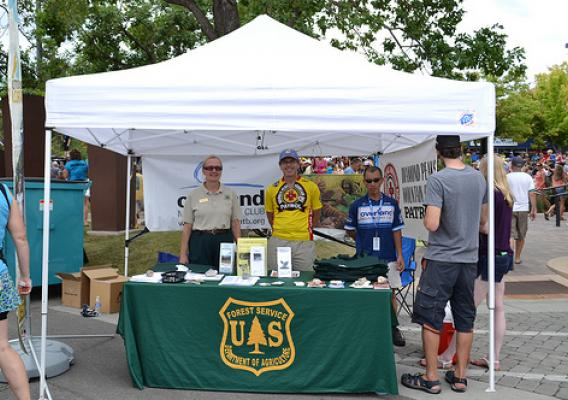 Kristy Wumkes (left), partnership coordinator on the Canyon Lands Ranger District, and volunteers greets visitors to the U.S. Forest Service booth at the Fort Collins stage finish line. (U.S. Forest Service/Reghan Cloudman)