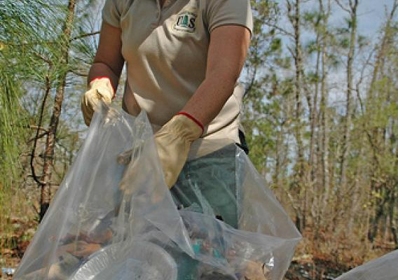 Recreation Technician Sherry Gaston of the Apalachicola National Forest bags trash littering the forest during Super-Clean Sweep. (U.S. Forest Service photo by Susan Blake)