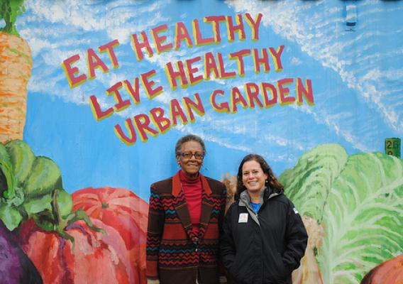 Livia Marqués and Juanita Ewell stand in front of the tool shed at Eat Healthy Live Healthy Urban Garden in the 900 block of Cherry Hill Road, Baltimore City, Maryland. The mural was painted by Towson University student John Rice.