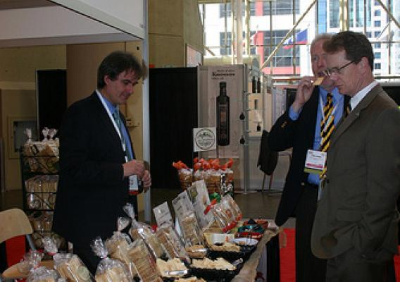 Antonio Galati, La Panzanella's director of business development (left), exhibits some of his company's specialty crackers, otherwise known as croccantini, to visitors attending the SIAL food trade show in Canada earlier this year. This Seattle-based company has expanded their international exports with help from USDA's Foreign Agricultural Service market export programs and by attending USDA-endorsed international food and trade shows. (Photo courtesy of USDA's Foreign Agricultural Service)