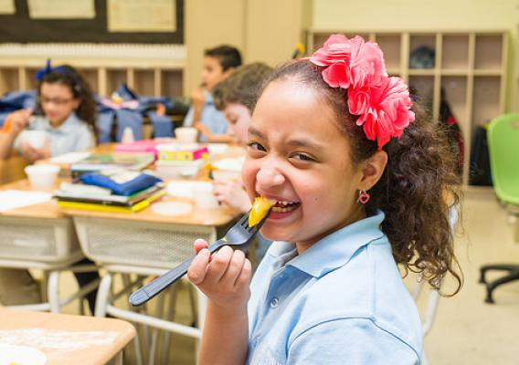 An elementary school student in West New York, New Jersey, enjoying a farm fresh bite of yellow tomato