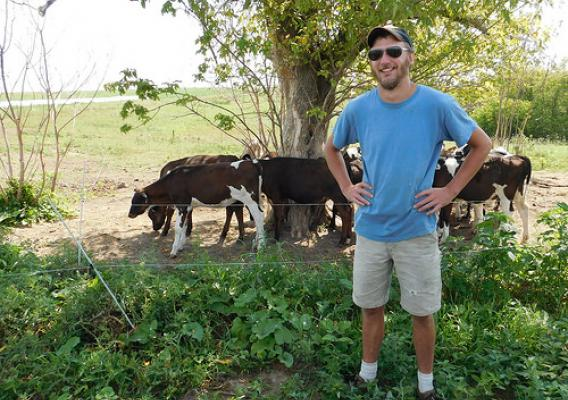 Reed Fitton with cattle and a tree behind him