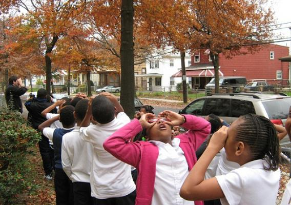 Students from the Paul Public Charter School in Washington, D.C., take to the streets pretending to use binoculars in search of their urban forest with a member of the Missoula (Montana) Chlidren's Theatre. The Missoula Children's Theatre works with the U.S. Forest Service to develop interactive, engaging performing arts school assemblies and workshops.