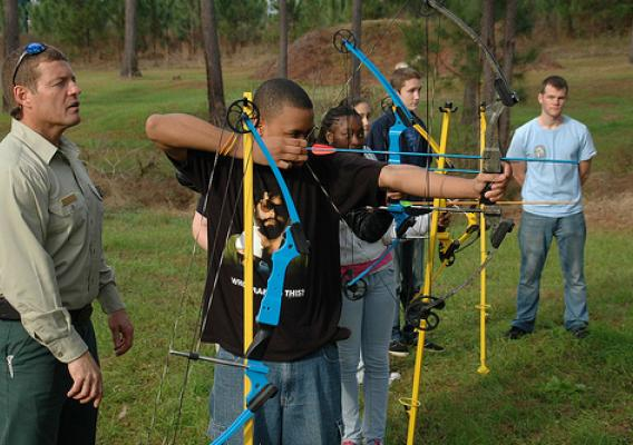 Natural Resource Manager Carl Petrick of the National Forests in Florida looks on as a high school student sets his sights on the archery range. Nearly 500 students from area schools attended the recent More Kids in the Woods event. (Photo Credit: Susan Blake, Public Affairs Specialist, National Forests of Florida)