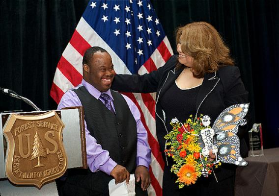 "Receiving the award for ""Communities in Conservation"" are Luisa Lopez, Counselor at El Valor and Vincent Jordan, participant in El Valor's Adults with Different Abilities Program. They are holding one of the products of this program—a monarch butterfly made for Día de los Muertos, or Day of the Dead."