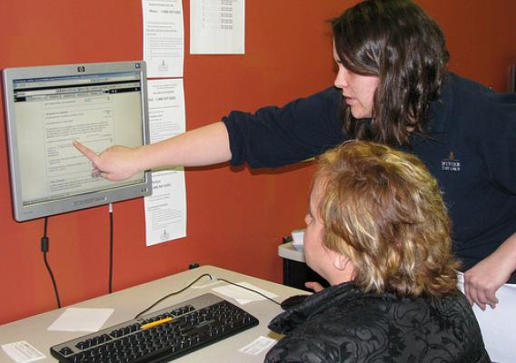 Hunger Task Force FoodShare Assistant Elizabeth Leister helps a client access benefits online at the Robles Center. Established in the 1970's, the Robles Center located in Milwaukee Wisconsin, was the first social services office serving Milwaukee's predominantly Latino south side.