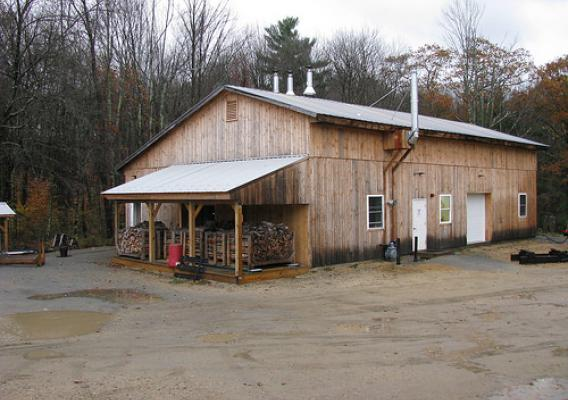 Harvard Forest staff renovated a pole barn to house the boiler room and modern wood shop. The new boiler room (left side of the building) contains three wood gasification boilers, a 2,500-gallon thermal storage tank, a propane-fired backup boiler and associated pumps and system controls. The sloped roof on the left of the building provides a dry storage area for racks of firewood prior to loading in the boilers. (U.S. Forest Service/Rob Clark)