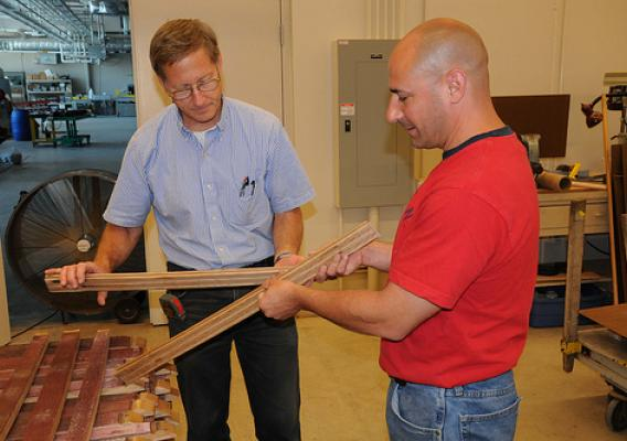 Forest Products Lab engineer John Hunt (left) and Jubliee Flooring owner Joe Triglia inspect flooring milled from discarded wine barrel staves.