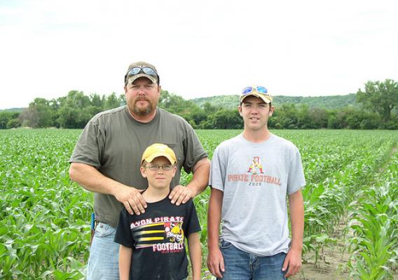 Joe Fillaus and sons, Cole and Carter, standing in front of their June 2013 corn crop after restoration was made to their field. USDA photo.