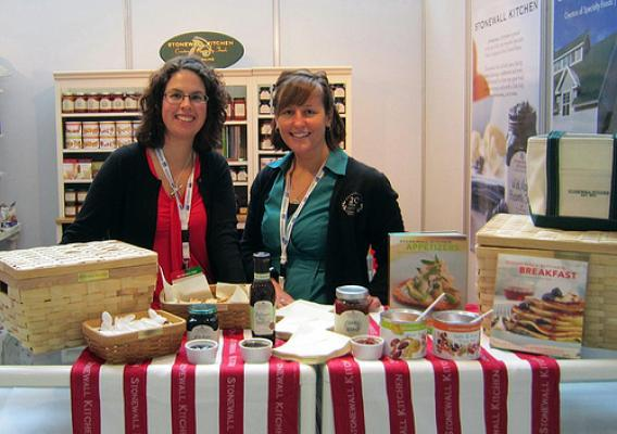 Carol Deeney (left), Stonewall Kitchen's international marketing director, and Stephanie Miller, Stonewall's social media and marketing coordinator, man a booth at the 2012 Gulfood Trade Show. The Foreign Agricultural Service's Market Access Program helps the specialty foods company participate in trade shows, which helps increase its international exposure and exports. (Courtesy Photo)