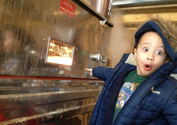 A youngster enjoying how maple syrup is made. NRCS photograph.